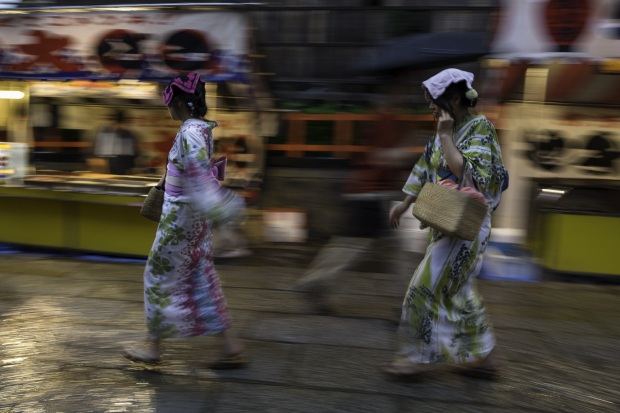 Girls in Yukata running through the rain with handkerchiefs on their heads, Japan.